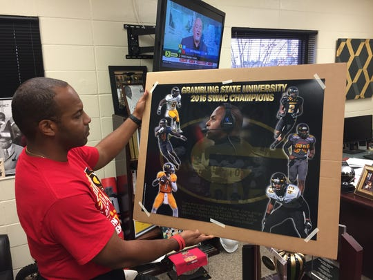 Grambling coach Broderick Fobbs holds up a new picture from the program's most recent win that captured the 2016 SWAC championship.