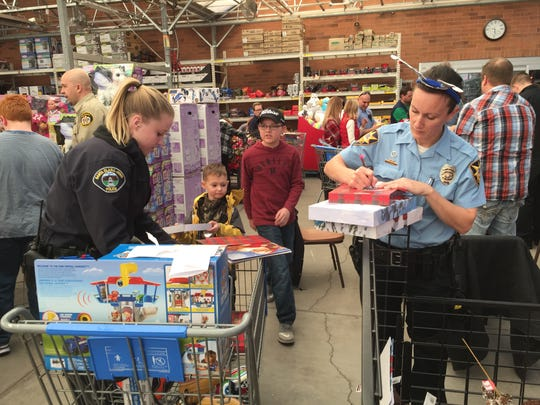 Santa Clara-Ivins Police Officer Hope O'Bray, left, and St. George Police Information Officer Lona Trombley help wrap children's gifts during Saturday's annual Shop With a Cop event in St. George.