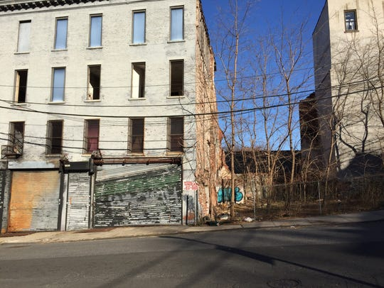 A vacant apartment building and and empty lot at 3-5