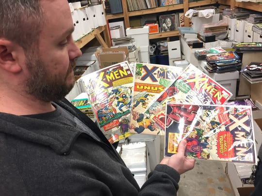 Jay's CD and Hobby owner Jason Shreve holds four vintage X-Men comics from the mid-1960s.