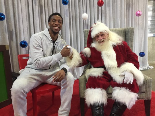 Pistons guard Ish Smith with Santa Claus at Tuesday's Toys for Tots event at Eastern Market.