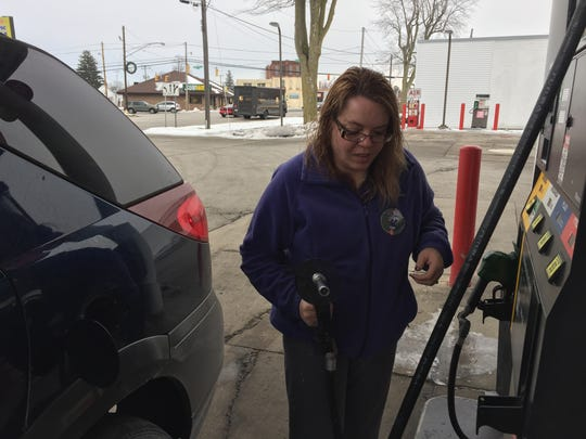 Lisa Haden, of Fremont, fills up her tank in preparation for her drive to Sandusky to celebrate Christmas with family.