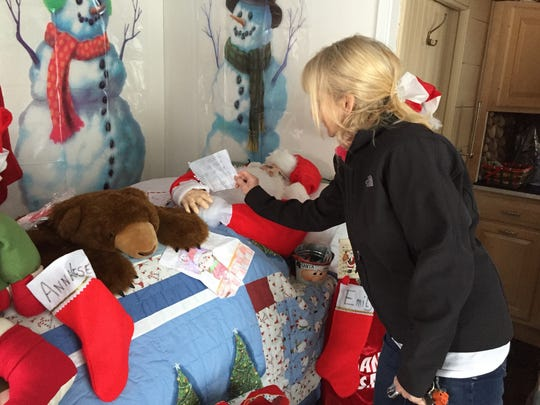 Jan Murphy adjusts a letter to Santa. Santa stays at