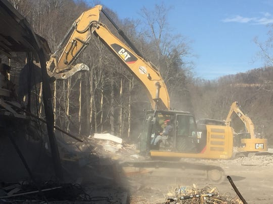 A trackhoe tears into the former Best Western Twin Islands on Friday.