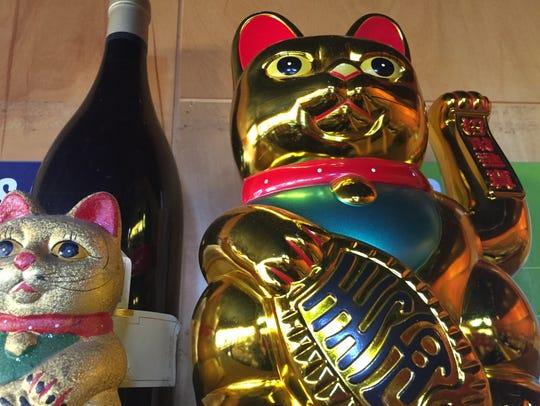 Asiana's maneki-neko or lucky cat sits over customer's