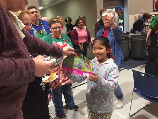 Yuseimi Ramirez, 8, was one of the prize winners at the Salvation Army's Christmas Dinner on Christmas Day 2016. Dinner organizer Lynne Newcomer estimated 700 people would come through.