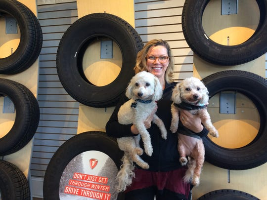 Dawn Tilghman, owner of  Burnett-White Tire Pros in Salisbury, holds two of her dogs, Sophie and Louie. The dogs visit the business every day.