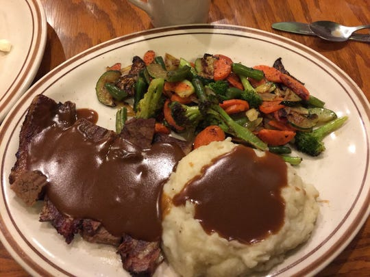 The popular smoked roast beef brisket dinner with mashed potatoes and grilled seasonal vegetables.