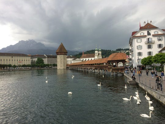 This June 15, 2016, photo provided by Albert Stumm shows swans and the Chapel Bridge in Lucerne, Switzerland. The compact city has preserved its medieval treasures of cobblestone squares, time-worn shops and frescoed houses. Lucerne turned up on Travel + Leisure's list of best 50 places in the world to travel in 2017.