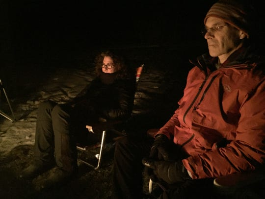 Linda Lomas and a community member sit at a bonfire