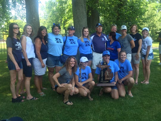 Richmond softball coach Howard Stuart stands with former