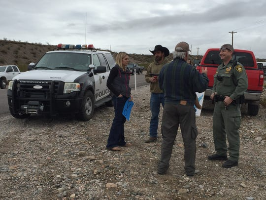 A Las Vegas Metropolitan Police officer visits with demonstrators Saturday near Cliven Bundy's ranch outside of Bunkerville, Nev. The group was protesting President Barack Obama's declaration of the Gold Butte National Monument encompassing a 300,000-acre area south of Mesquite on Wednesday.