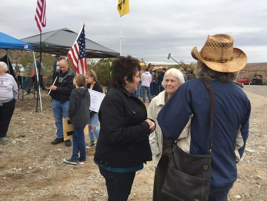Carol Bundy, center, visits with demonstrators near
