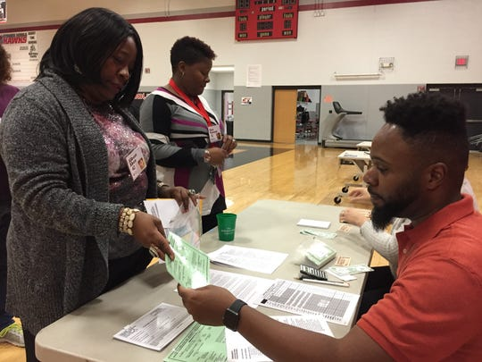 Reggie Carruth, who ran a check-cashing establishment during a poverty simulation a La Vergne Middle, talks with Janice Adams.