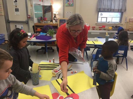 Judy Klima hands out shapes for students to glue and experiment with layering at the Integrated Arts Academy on Jan.3, 2017.