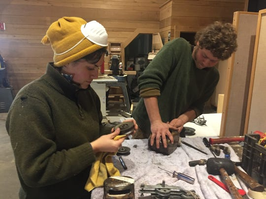 Grace Glynn of Saco Maine, an educator and deckhand with Clearwater, and Dylan Kane of New Haven, Connecticut, a deckhand, work on pulleys from the sloop Clearwater at the organization's Kingston Home Port.