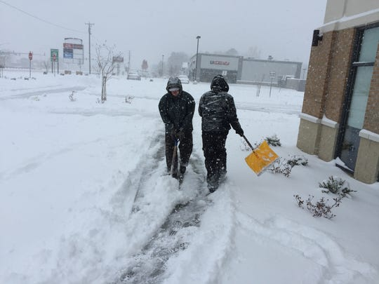 William Hall and Dylan Assadi of 2ADH LLC property management shovel snow off the walk Saturday morning in front of the new Aspen Dental in Salisbury off Route 13 on Jan. 7, 2017.