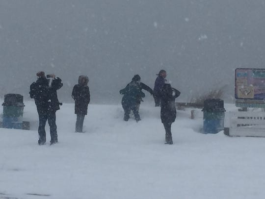 People frolic in the snow at Rehoboth Beach on Saturday.