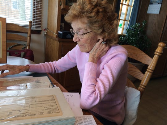 Donna Janecek looks over information about her long-dead brother.