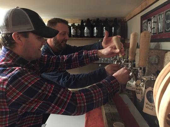 Co-owners Peter McAlenney (foreground) and Jeremy McMullen dispense beer last week at Red Barn Brewing in Danville.