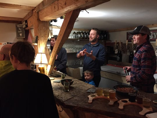 From left to right, Erin and Jeremy McMullen, with their 4-year-old son, Oden, and Peter McAlenney interact with customers last Friday at Red Barn Brewing in Danville.