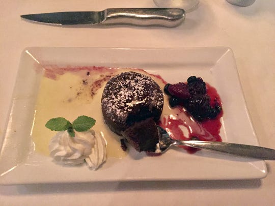 A fudgy, flourless chocolate cake with trimmings at St. Germain Steakhouse