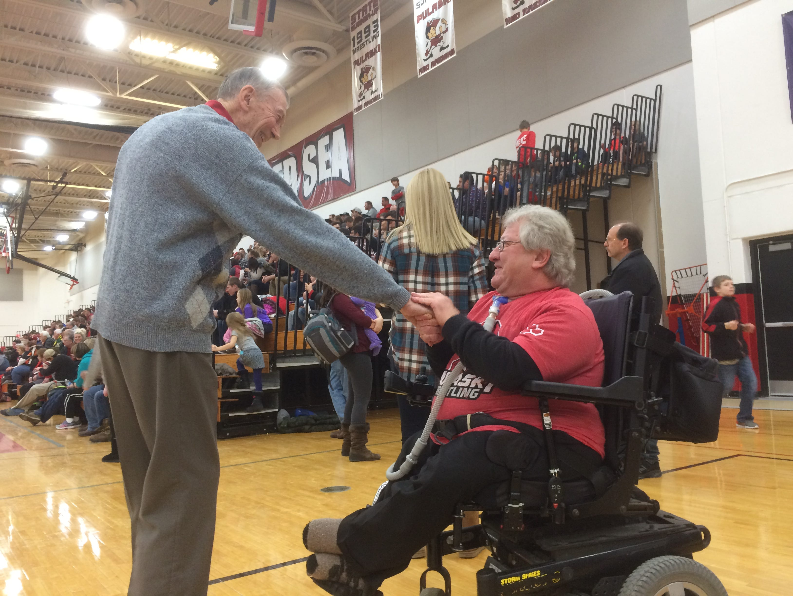 Gerald Lasecki, right, is greeted by Emil Ripley last Thursday at the Pulaski wrestling team's alumni night. Lasecki was announced as the recipient for the National Wrestling Hall of Fame's Medal of Courage.