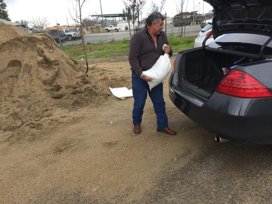 Jose Sanchez places a sand bag in his car's trunk Thursday morning. Visalia is hosting a free, self-service sand bag station ahead of the storm systems expected to move through the area.