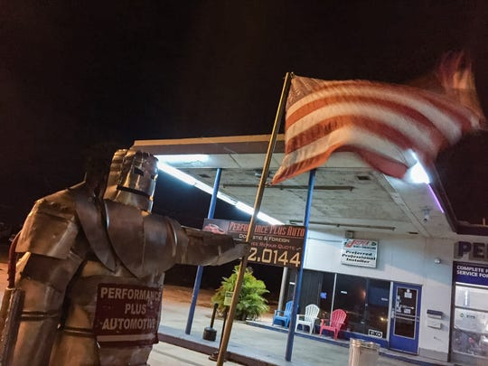 An armored statue holding the American flag at Performance Plus Automotive on U.S. 1, in Cocoa as winds increase Sunday night.