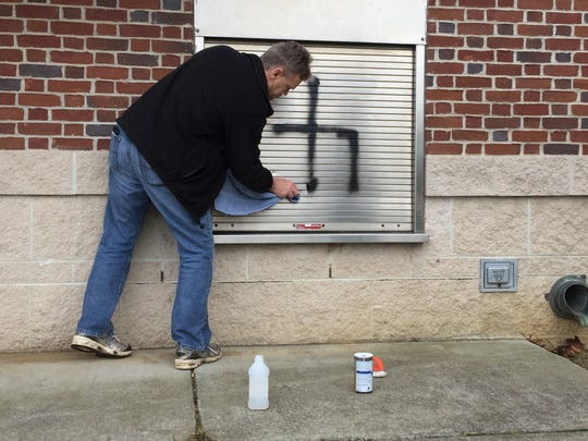 Hyde Park resident Steve Saunders got an old towel and a bottle of rubbing alcohol to clean up some of the graffiti.