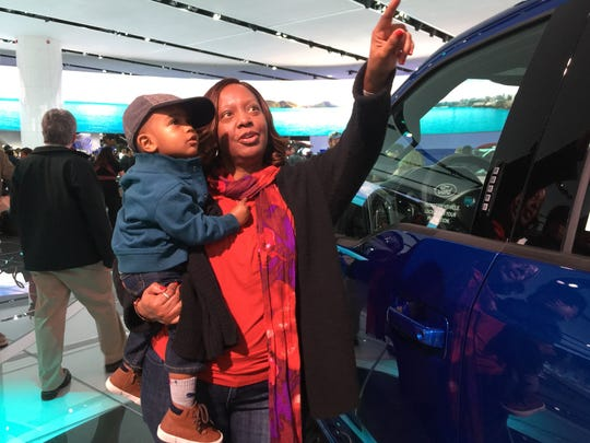 Deborah Black of Redford Township and her grandson Jace Berry, 2, stand near a Ford F-150 pickup and check out digital video screens at the automaker's display on Sunday, Jan., 22, 2017, at the North American International Auto Show at Cobo Center in Detroit.