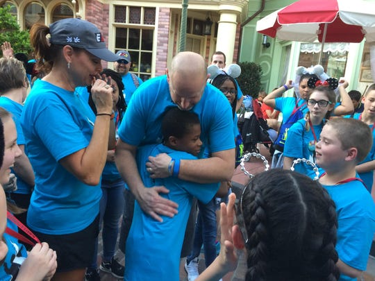 McGary student Devontae Johnson hugs Evansville Police Department Sgt. Jason Cullum as Cullum's wife, Shelly, and Glenwood student Cod Rahm look on.  Moments before a large group of students had embraced Cullum in a group hug after he was recognized as the veteran of the day on Saturday at the Magic Kingdom.