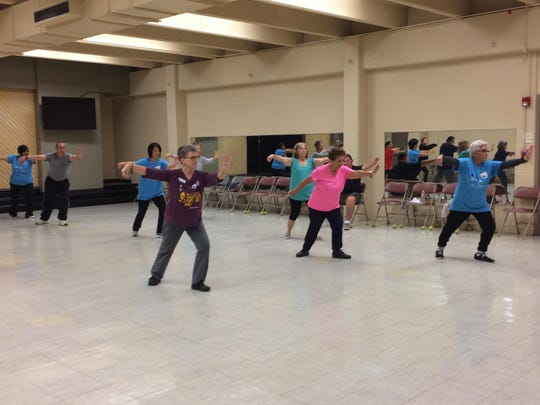 Residents participate in a senior fitness tai chi class.