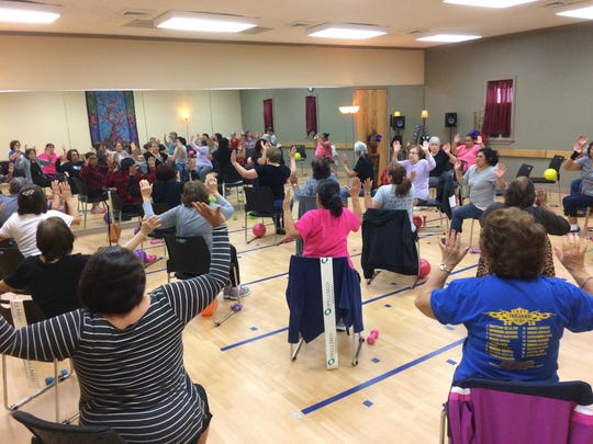 Residents participate in a senior fitness strength-training class called Easy Up, Easy Down.