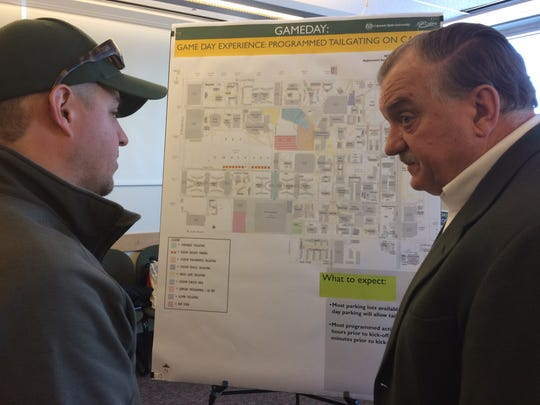 Aaron Garcia talks to Doug Max, CSU's senior associate athletic director for facilities and events, about plans for parking and tailgating at the new on-campus stadium during an open house Friday at the Lory Student Center.
