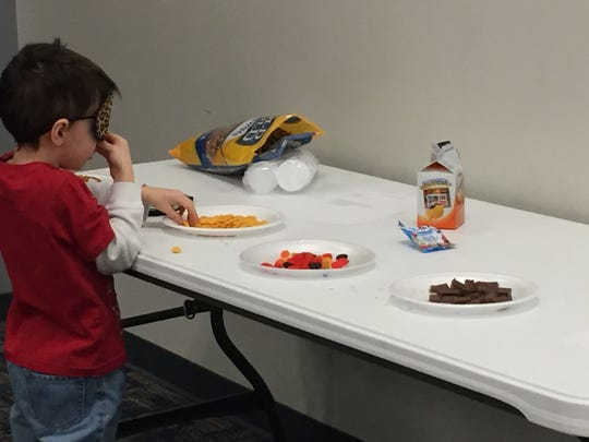 """Kieran Leiter, 5, tries out an activity at the """"taste"""" station at an afterschool program at the Vestal Public Library."""
