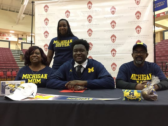 Toledo Central Catholic senior defensive lineman and future Michigan Wolverine James Hudson III, center, is joined by his mother, Glenda, left, older sister, Ciara, and father, James Hudson Jr., at a signing ceremony at his high school on Wednesday, Feb. 1, 2017.