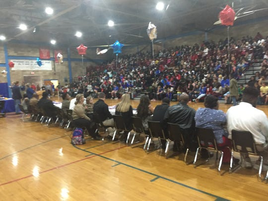 A packed student assembly inside Pine Forest gym cheered