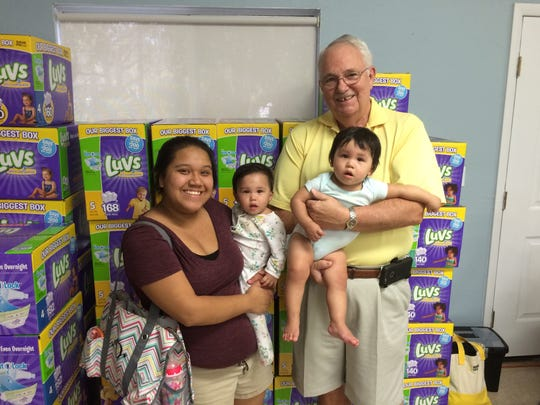 Volunteer Wayne Antworh with two little ones who receive Baby Basics diapers, and their mom. The organization helps working families with the monthly expense.