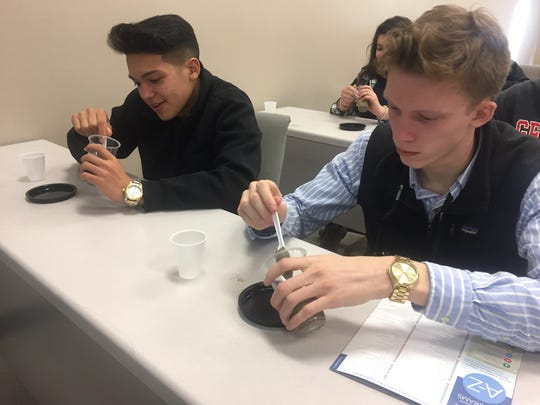 Alberto Ortiz, left, and Connor Anderson, both Blackman High School Collegiate Academy students, mix up concrete to make a coaster when they visited Middle Tennessee State University Feb. 2, 2017.