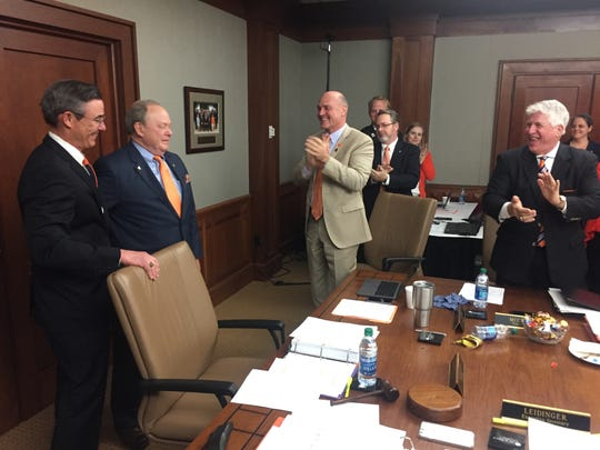 Clemson Board of Trustees Chairman Smyth McKissick (left) honored Bill Hendrix (second from left) at Friday's meeting while President Jim Clements, board member Nicky McCarter and the rest of the room applauded.
