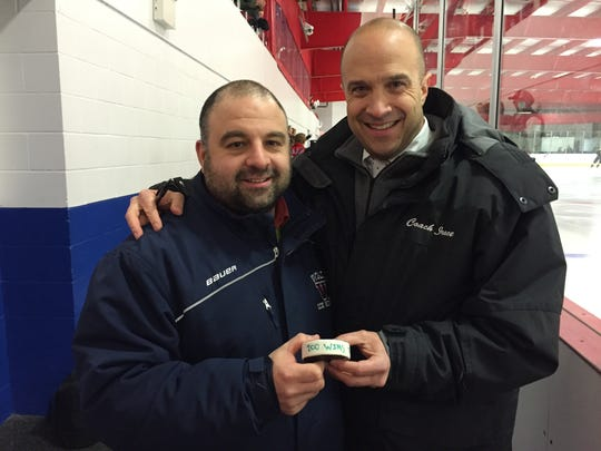 Head Coach Mike Dianora (left) and Assistant Coach Rick Irace (right) holding the game puck from Wall Township 200th victory in program history.