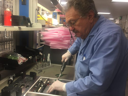 Dominick Romano of Newark, an assembly technician at Hologic's facility near Glasgow, builds a detector that will be used in a 3-D mammography machine.