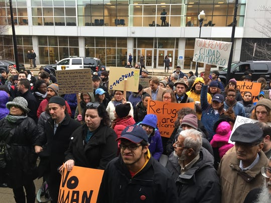 Protesters with pro-immigrant signs gather in front