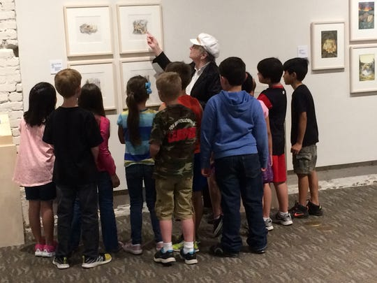 A docent leads students on a tour of the 2015 Marla