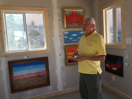 Painter Gene Poe speaks to a group of visitors at his Cathedral City studio, which he just finished building last week.
