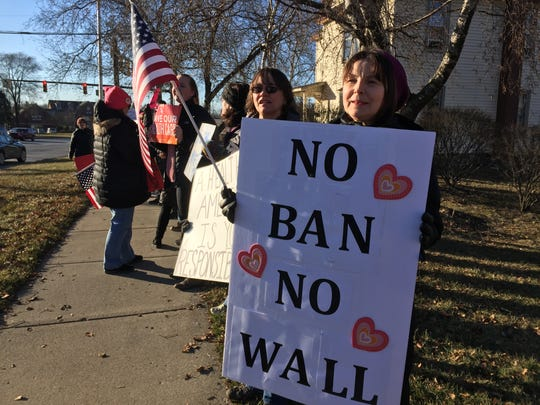 Okemos resident Joanne Guertin, right, and Lansing resident Katherine Erickson, middle, were among dozens of protesters who lined the sidewalk in front of U.S. Rep Mike Bishop's Brighton office on Feb. 13.