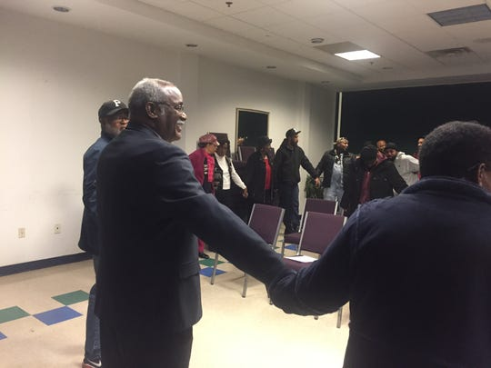 City Councilman Samuel L. Guy held hands with residents