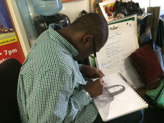 Derrick Freeman drawing one of his 'Mona Lisa' figures