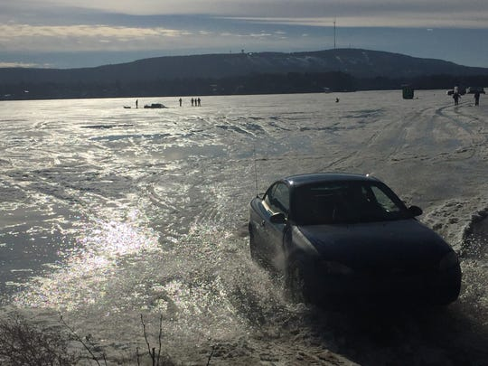 A car leaves the ice of the Wisconsin River after a truck fell through Saturday afternoon.